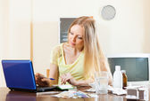 Woman reading about medications on laptop in internet — Stockfoto