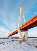 Cable-stayed bridge across frosty river — Stock Photo