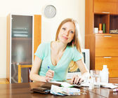 Long-haired blonde woman with medications and money — Stock Photo