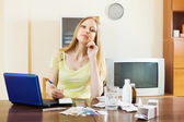 Young woman counting the cost of medications — Stock Photo