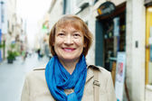 Smiling mature woman in city street — Stock Photo