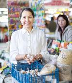 Mogen kvinna köper vitlök för plantering — Stockfoto