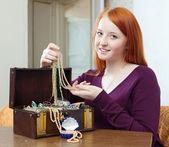 Teenager girl looks jewelry in treasure chest — Stock Photo