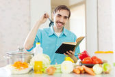 Man ladle pan and cookbook in kitchen — Stock Photo