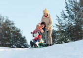 Two women with child sliding on sleds — 图库照片