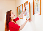 Woman in red hanging the art pictures — Stock Photo