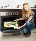 Long-haired housewife cooking fish on sheet pan in oven — Photo