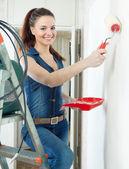 Vrouw in amerikaanse overalls verven muur — Stockfoto