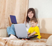 Woman with toddler using laptops in living room — Stock Photo