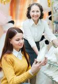 Девушка выбирает белые туфли в магазине — Стоковое фото