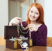 Red-headed girl looks jewelry — Stock Photo