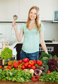 Beautiful woman cooking with ladle from vegetables — Stock Photo
