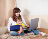 Happy woman and child with laptops — Stockfoto