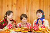 Happy mother with daughters eating pancake — Stock Photo