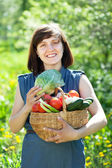 Happy woman with basket of harvested vegetables — Stock Photo