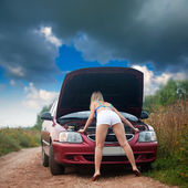 Sexy girl looking under car hood — Stock Photo