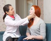 Female doctor touching neck of teen — Stock fotografie