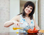 Woman pouring oil to salad at home — Stock Photo