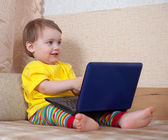 Toddler sits with laptop — Stockfoto