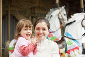Mother with girl against carousel — Stock Photo