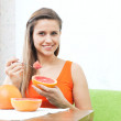 Woman eating grapefruit with spoon — Stock Photo