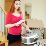 Женщина, чтение гарантийного талона для новых кухонный агрегат — Стоковое фото #30994603