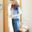 Blonde woman with luggage loocking door lock — Stock Photo