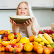 Happy blonde girl holding melon — Stock Photo