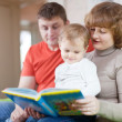 Parents with child looks the book — Stock Photo #30995001