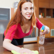 Happy long-haired girl in red dusting table — Stock Photo #30995199