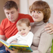 Parents with child looks the book — Stock Photo #30995419