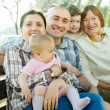 multigeneration family on bench in summer park — Stock Photo