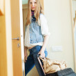 Sad woman with luggage leaving  home — Stock Photo