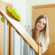 Smiling womdusting stair railings — Stock Photo #30995943