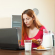 Cute girl checking e-mail in laptop during breakfast time at hom — Stock Photo