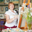 Female artist paints a picture on canvas — Stock Photo