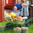 Man and two women with  vegetables in garden — Stock Photo