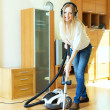 Happy long-haired woman in headphones cleaning with vacuum clean — Stock Photo