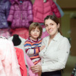 Mother with baby at clothes store — Stock Photo