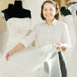 Shop consultant shows bridal dress  — Stock Photo