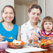 Women with girl eats vegetables salad — Stock Photo #30996577