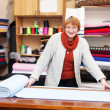 Saleswoman measures the fabric — Stock Photo