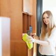 Happy blonde long-haired woman wiping the dust — Stock Photo