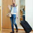 Positive woman with luggage in home — Stock Photo