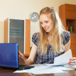 Positive long-haired woman working with documents and laptop — Stock Photo #30997317