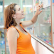 Stock Photo: Pregnant womat pharmacy drugstore