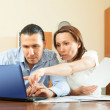 Couple staring financial documents in home — Stock Photo #30997481