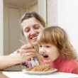 Mother with chil eats buckwheat porridge — Stock Photo