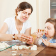 Happy mother and baby  sculpting from clay at table — Stock Photo