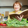 Mature woman cooking okra with cookbook i — Stock Photo
